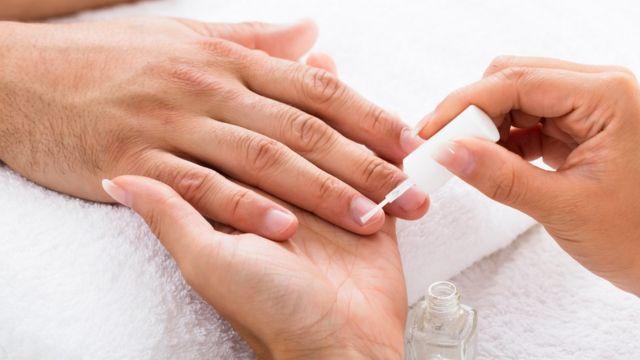 Mujer practicando manicura a hombre.