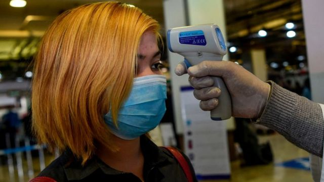Una mujer es examinada con un termómetro en un aeropuerto.