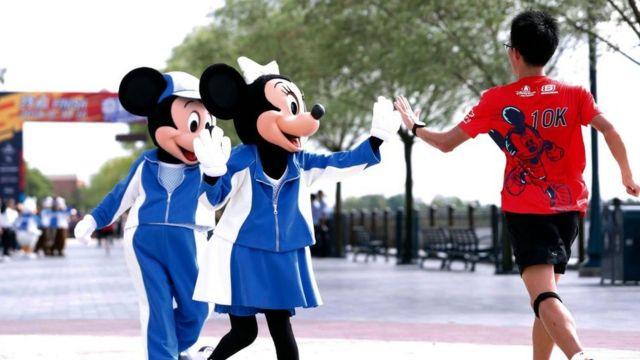 Mickey y Minnie Mouse saludando a un niño.