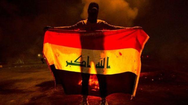 متظاهر ملثم يحمل علم العراق