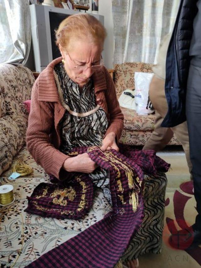 Mulher costurando estola que será usada pelo papa Francisco na Igreja Al-Tahira