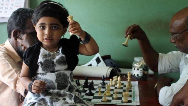 Una niña sosteniendo una pieza blanca. Al fondo, dos hombres juegan una partida de ajedrez