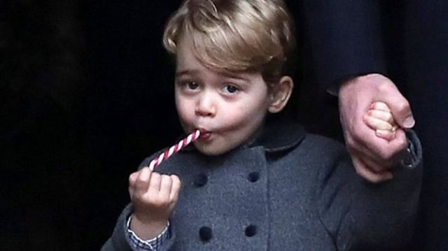 25 December 2016: George is given a candy cane after leaving the morning Christmas Day service at St Mark's Church, Englefield, near his maternal grandparents' home at Bucklebury, Berkshire