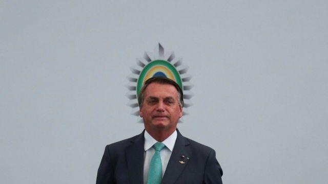Bolsonaro em pé em frente a painel com símbolo brasileiro