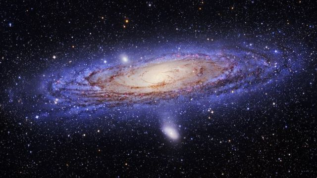 A spiral galaxy with blue/purple dust in its outer arms and reddish dust in its interior