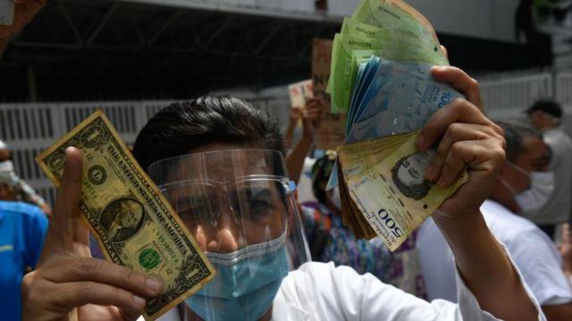 Un hombre sostiene un dólar y un puño de bolívares