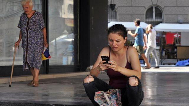 žena drži telefon u Beogradu