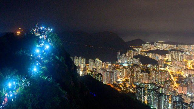 Участники акции зажигают фонарики на вершине Львиной горы