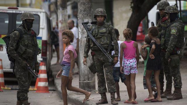 Soldados em meio a crianças em ruas do Rio de Janeiro