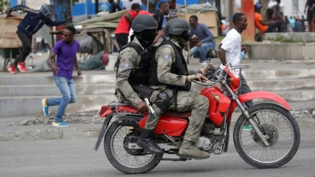 Protesters and masked men in Haitian National Police uniforms run away during a shooting in Champ de Mars, Port-au-Prince, Haiti February 23, 2020.