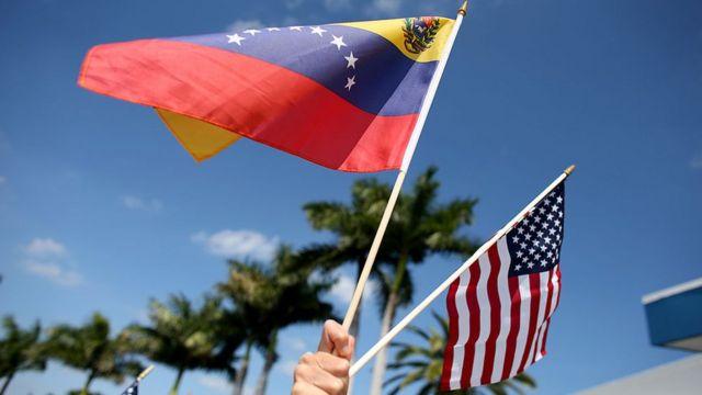 Una persona sostiene dos banderas, de Estados Unidos y Venezuela.