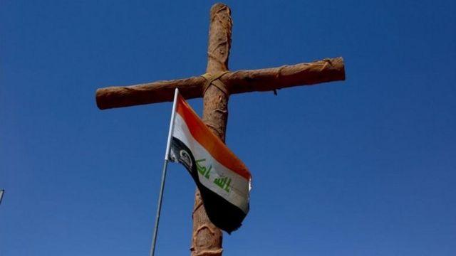 العلم العراقي يعانق الصليب