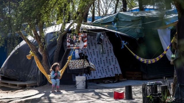 A Salvadorian girl sits near a Biden-Harris campaign poster inside a camp for asylum seekers on February 07, 2021 in Matamoros, Mexico