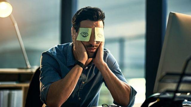 Un hombre sentado frente a la computadora, el rostro entre las manos, y dos post its en los ojos con dibujos de... ojos