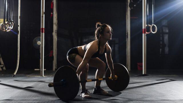 Mulher se prepara para levantar peso em academia