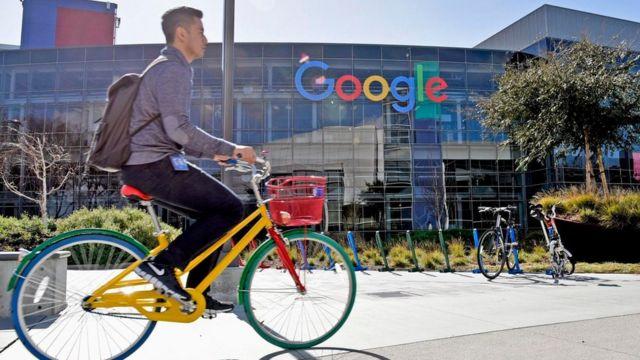 Una persona montando una bicicleta frente a las oficinas centrales de Google en Silicon Valley