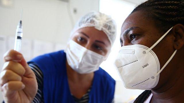 Enfermeira mostra seringa com líquido para mulher
