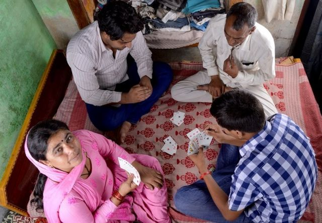 Rural Indian Family Playing Cards at Home on the Bed