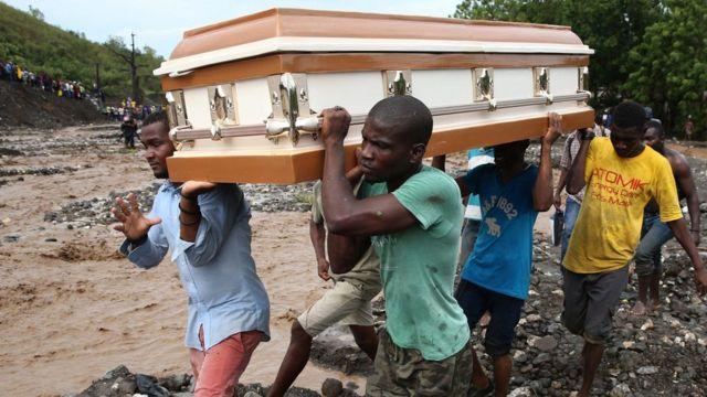 Hombres cargan un féretro mientras atraviesan un río en Haití