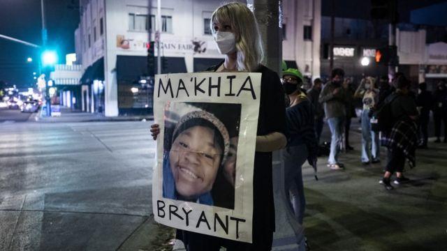 Una mujer con un cartel en recuerdo a Ma'Khia Bryant, joven de 16 años baleada en Ohio