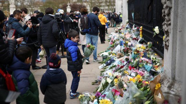 Personas dejan flores y recuerdos a las puertas del palacio de Buckingham