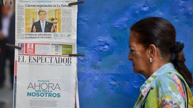 Una señora pasa por un quiosco de prensa en Colombia