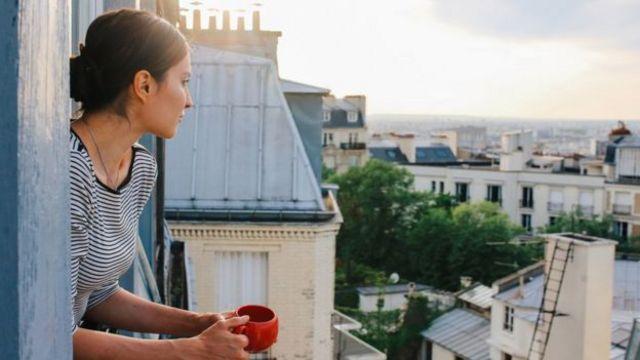 Девојка пије кафу на пророру у рано јутро