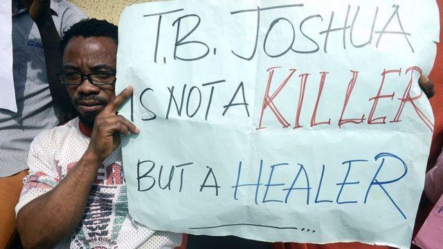 Un homme handicapé tient une pancarte pour protester contre l'enquête du coroner le 30 octobre 2014 lors de l'audience à la Haute Cour d'Ikeja à Lagos sur la cause de l'effondrement du 12 septembre dans une maison d'hôtes de la Synagogue Church of All Nations.