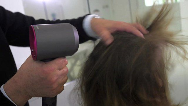 A man drying hair using a Dyson hairdryer