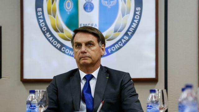 Bolsonaro sentado em reunião, em frente a painel com emblema das Forças Armadas