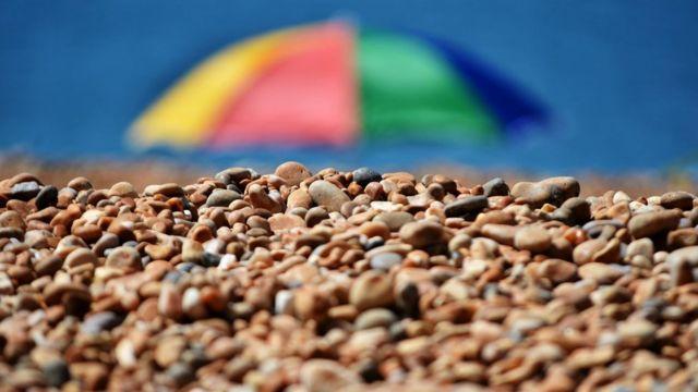 Piedras y una sombrilla en la playa.