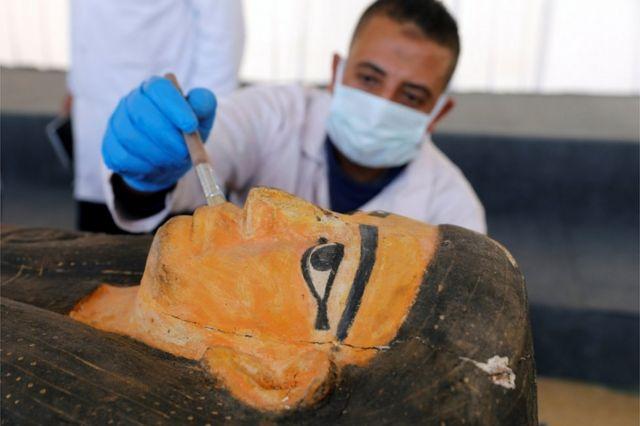 عالم آثار ينظف تابوتاً حجرياً اكتشف في منطقة سقارة بمصر