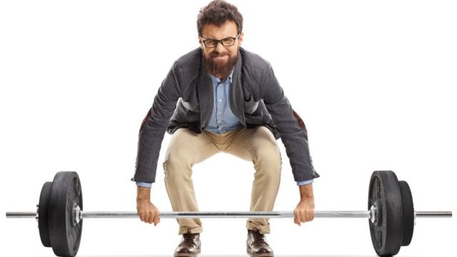 Homem com roupa casual levantando uma barra de peso livre