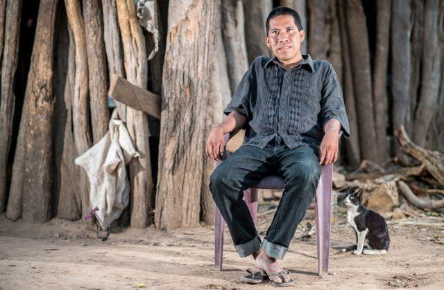 Chagabi Etacore sentado em uma cadeira na floresta com um gato ao lado dele