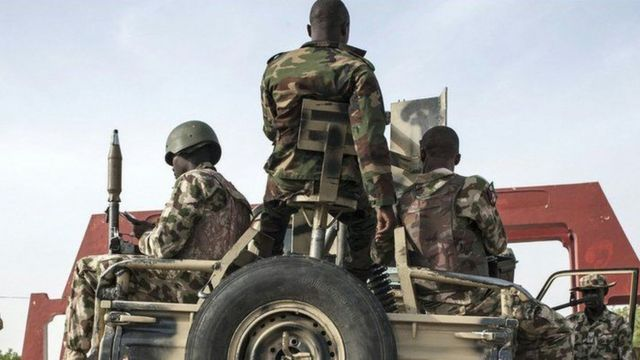 Nigerian soldiers dey on top and around car