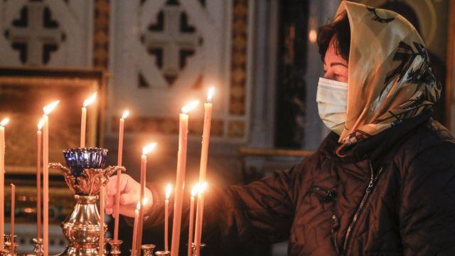 Женщина в маске в церкви