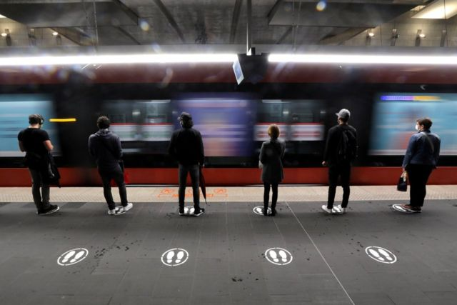 People stand on markers on a tramway platform