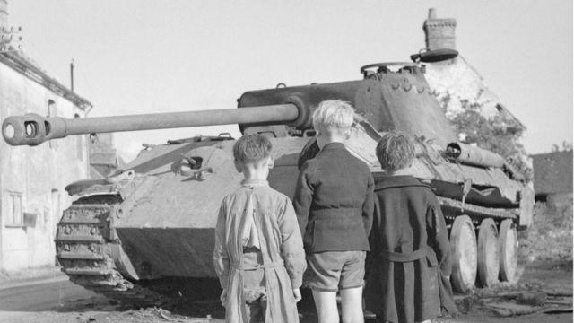Meninos franceses diante de tanque alemão após derrota de nazistas na França