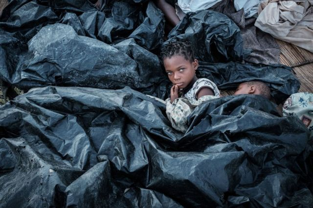 Девочки укрываются от дождя в приюте в Мозамбике