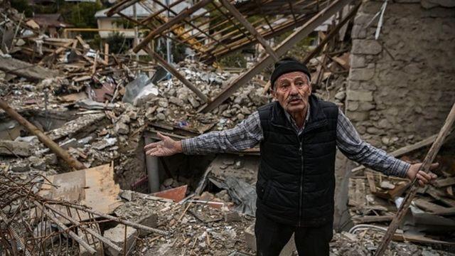 Xankəndində dağıdılmış evinin qarşısında duran kişi
