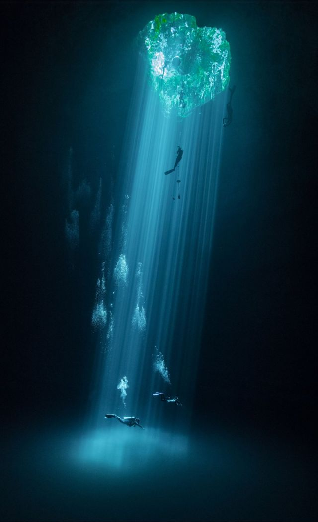 Divers swim in water-filled sinkhole