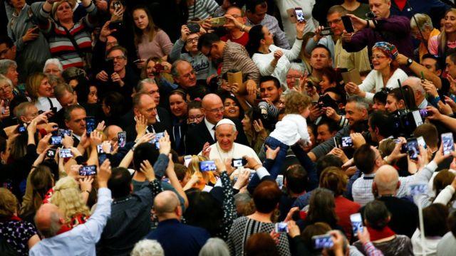 O papa Francisco em meio a uma multidão de fiéis com câmeras e celulares