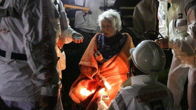 Elderly woman with rescue workers