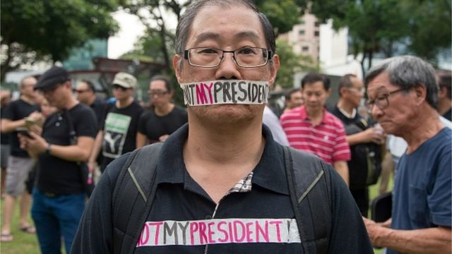 A man takes part in a protest against the walkover victory of Halimah Yacob as Singapore's President at Hong Lim Park in Singapore on September 16, 2017. Hundreds of Singaporeans angered by the walkover victory of its first female president gathered in a downtown park