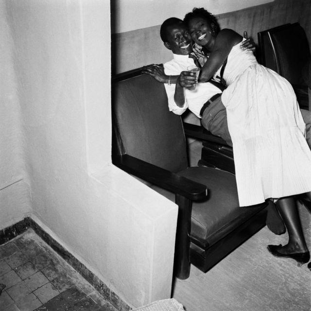 Un jeune homme et une jeune femme, tout sourire, s'embrassent devant la caméra.