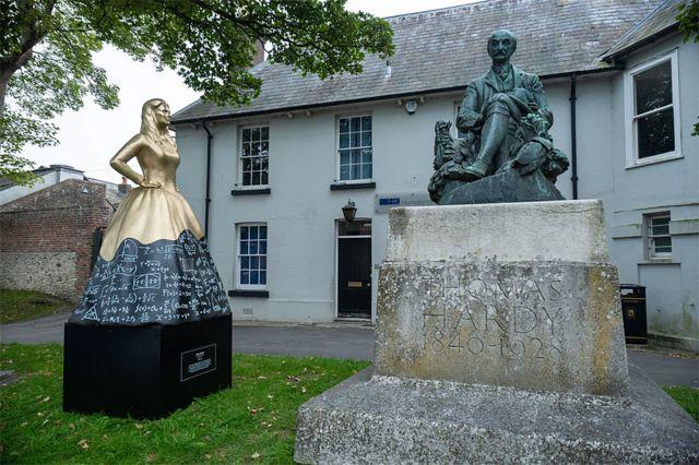 Mary em frente à estátua de seu irmão, o escritor Thomas Hardy, em Dorchester, na Inglaterra