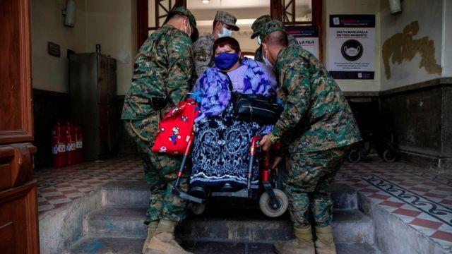 soldados ayudan a una mujer en silla de ruedas