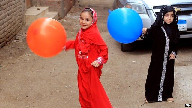 Girls carry colourful balloons
