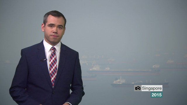 Still from weather presenting video - Ben Rich with hazy photograph from Singapore in the background