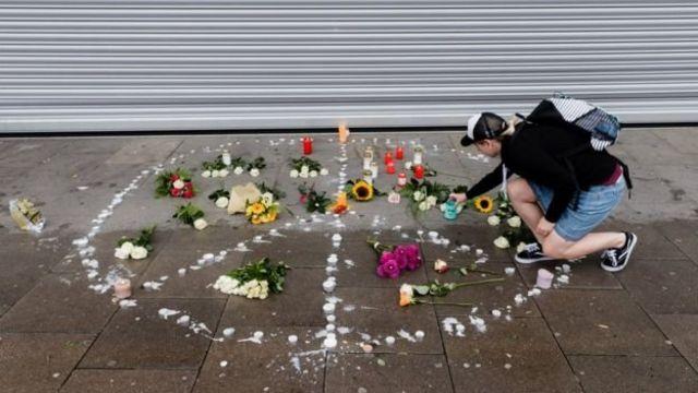 شموع وزهور على شكل علامة السلام في منطقة الحادث لتأبين ضحية الهجوم